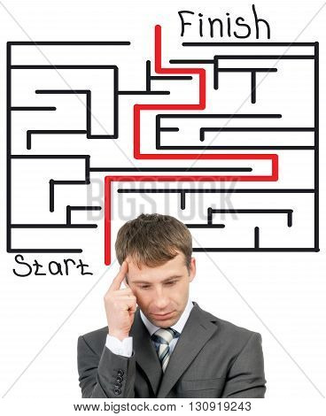 Thinking businessman in front of labyrinth with red line showing the way out