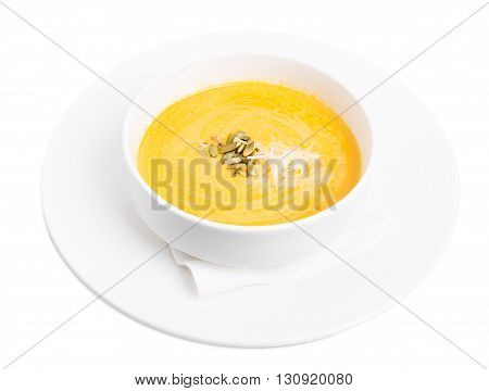 Pumpkin cream soup with grated cheese and seeds. Isolated on a white background.