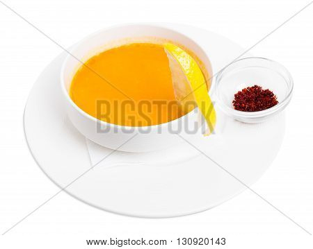 Lentil soup cream with lemon slice and dried minced paprika spice. Isolated on a white background.