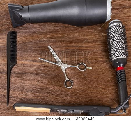 Hair dryer, curling iron, comb and scissors on a background of brown hair.