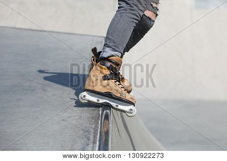 Aggressive Inline Rollerblader Grinding On Ramp In Skatepark