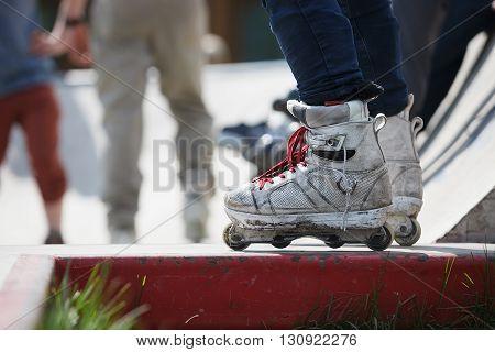 Aggressive Inline Rollerblader Standing On Ramp In Skatepark