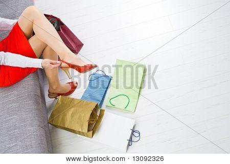 Junge Frau auf Couch Schuhe, bunte Einkaufen auf dem Boden sitzen.