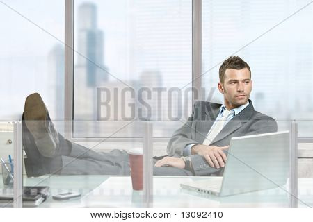Casual businessman sitting at desk in front of office windows, thinking.