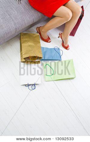 Junge Frau auf Couch nach Einkaufsbummel, bunte Einkaufen auf dem Boden sitzen.
