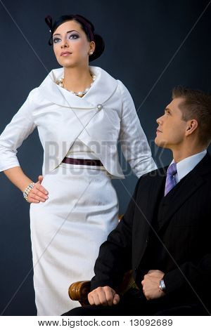 Portrait of young couple dressed in elegant clothes. Woman wearing white cocktail shirt with jacket, man wearing three-pieces dark suit.