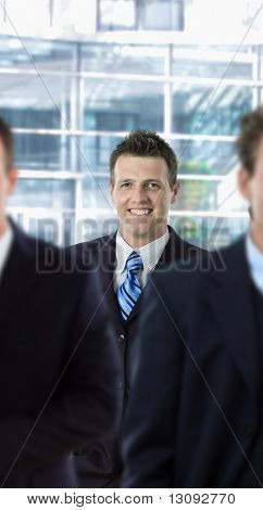 Happy businessman standing behind other businesspeople, in front of office building.