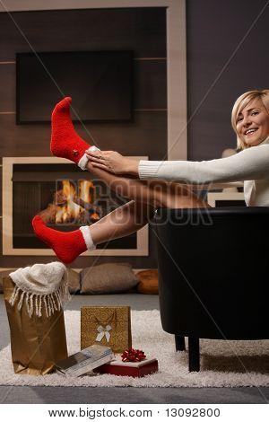Frau, die Vorbereitung auf Weihnachten, Weihnachtsmann ziehen Socken vor Kamin. Geschenke auf das floo