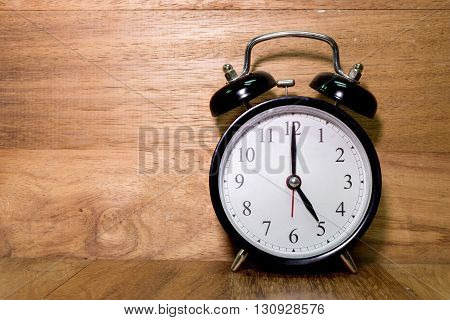 Vintage background with retro alarm clock on wood background Alarm clock shows Five o`clock