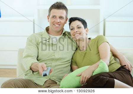 Young couple watching TV at home sitting pn sofa.
