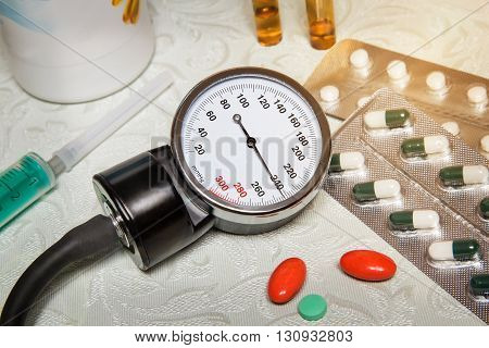On the table is an apparatus for blood pressure measurement which shows higher pressures. It's a hypertensive crisis. Near are medications to assist. poster