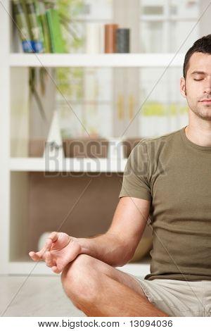 Человек делает йога упражнения дома, сидя на полу в гостиной, половина портрет.