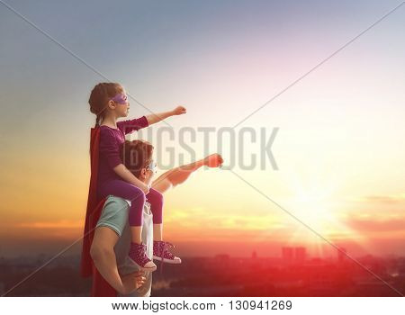 Happy loving family. Father and his daughter child girl playing outdoors. Daddy and her child girl in an Superhero's costumes. Concept of Father's day.