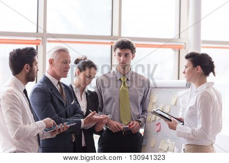 young startup businessman making presentation of project to senior investior, group of business people taking notes and make plans on white  flip board and tablet computer