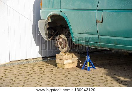 Jacked-up vehicle with car jack and dismounted wheel gives a clear view of the wheel bearing.