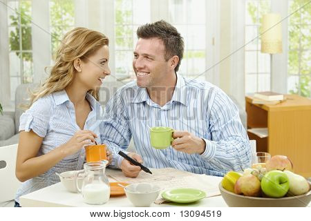 Happy couple drinking coffee at home, sitting at breakfast table, looking at each other, smiling.