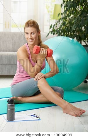 Young woman doing bicesps exercis with dumbbell sitting on fittness mat at home, smiling.