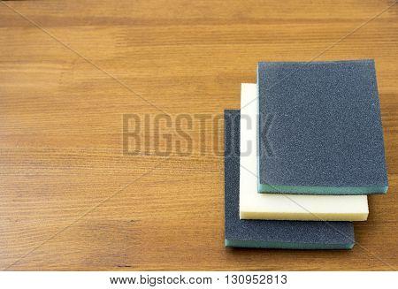 Sanding sponge on polishing paper abrasive materials on wooden background.