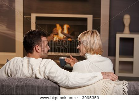 Young romantic couple sitting on sofa in front of fireplace at home, looking at each other, talking, rear view.