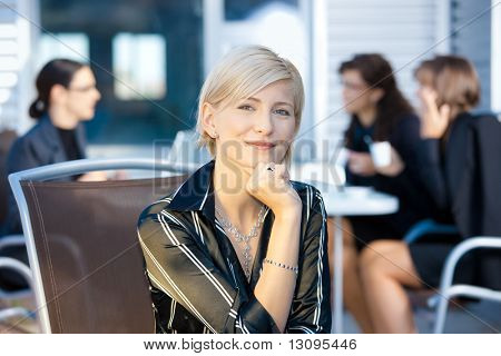 Portrait of happy young businesswoman sitting in chair, smiling.