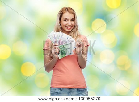 money, finances, investment, saving and people concept - happy young woman with euro cash money over summer green lights background