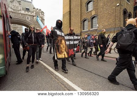 LONDON - ENGLAND 1ST MAY 2016 - An anarchist group with a slogan and masks move across Tower Bridge in London during the May Day Bank Holiday rally on the 1st of May 2016.