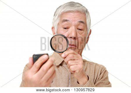 portrait of senior Japanese man with presbyopia on white background