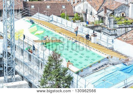 Udine Italy - May 3 2016 : Construction crew working on the roof sheeting