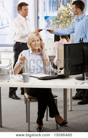 Young businesswoman sitting at office desk, talking on mobile phone.