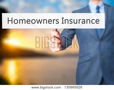 Homeowners Insurance - Businessman Hand Holding Sign