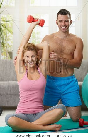 Couple doing dumbbell exercise sitting on fittness mat at home, smiling.