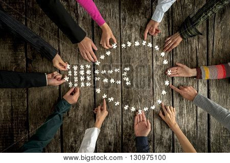 Teamwork and cooperation concept - group of twelve people male and female assembling a light bulb shape with blank puzzle pieces on a rustic textured desk top view.