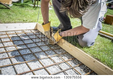 Closeup of a man making a net of steel bars by clipping them together with a wire and pliers placing it in as a reinforcement in a rectangular hole for a concrete foundation outside in backyard.