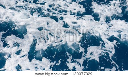 Restless foamy blue sea water with splash