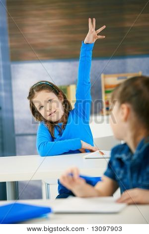 Portrait of smiling elementary age schoolgirl raising hand in class.