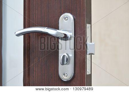 chrome door handle on interior brown door with latch