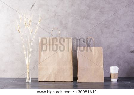 Take away food bags wheat spikes and coffee cup on concrete background. Mock up
