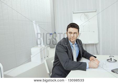 Junge Architekt arbeiten am Schreibtisch, lächelnd.