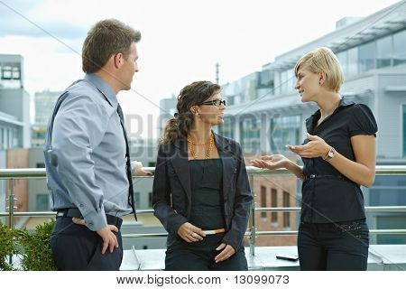 Business people having break and talking on terrace of office building.