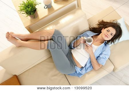 Girl resting on couch with feet up, smiling, holding coffee cup, in overhead view.
