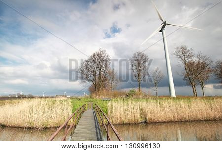 bridge via river and wind turbine over sky on Dutch farmland