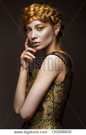 Beautiful girl in a gold dress with creative makeup and braids on her head. The beauty of the face. Photos shot in the studio.
