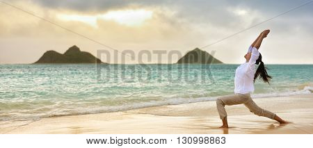 Yoga woman meditating in warrior I pose at hawaiian beach during beautiful morning sunrise against Lanikai mountains Hawaii landmark. Banner panoramic crop for advertisement.