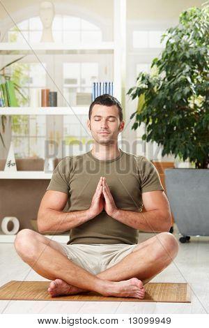 Mann zu Hause Yoga Übungen, sitzen am Boden im Wohnzimmer.