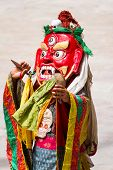 Unidentified monk with phurpa (ritual knife) performs a religious masked and costumed mystery dance of Tibetan Buddhism during the Cham Dance Festival in Hemis monastery, India. poster