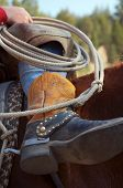 upcolse phot of a cowboy sitting on his horse showing mostly his boots and rope in a relaxed casual way poster