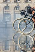 People riding bicycles in the mirror fountain in front of Place de la Bourse in Bordeaux France poster