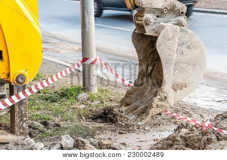 Excavator Machinery Bucket With Dirt And Mud On The Street Construction Site Prepared For Digging An