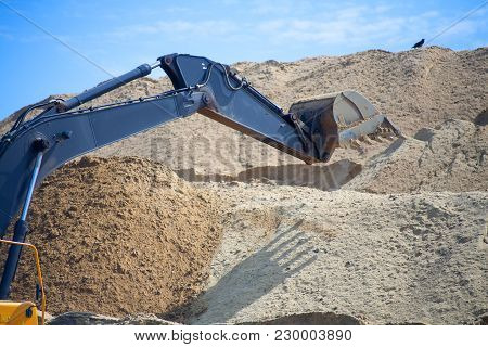 A Large Iron Excavator Bucket Collects And Pours Sand Rubble And Stones In A Quarry At The Construct