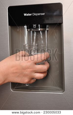 A Woman's Hand Holding A Glass, And Water Pouring In To It Out Of A Water Dispenser
